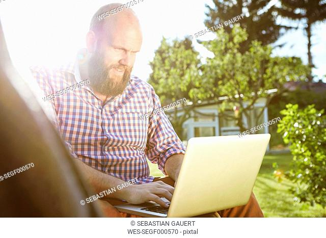 Young man working with laptop in garden