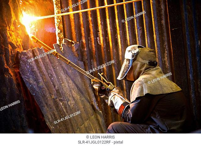Welder at work in steel forge