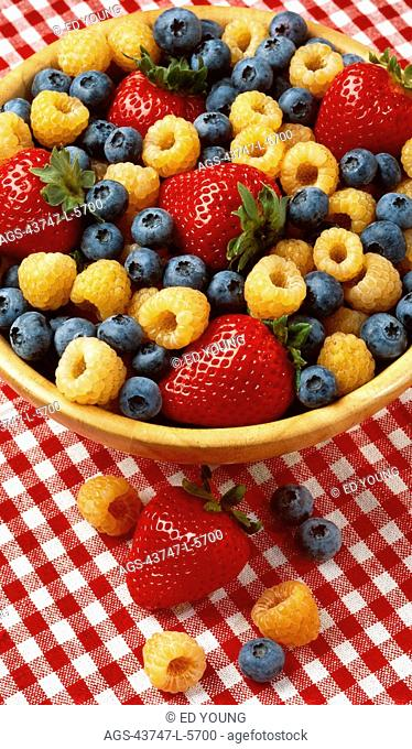 Agriculture - Strawberries, golden raspberries and blueberries in a wooden bowl on a red checkered tablecloth