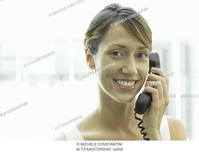 Woman using landline phone, smiling at camera