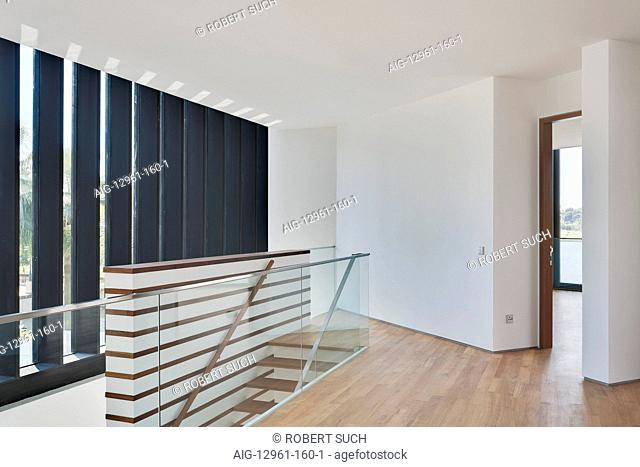 Modern white landing at top of stairs with timber floor and open door