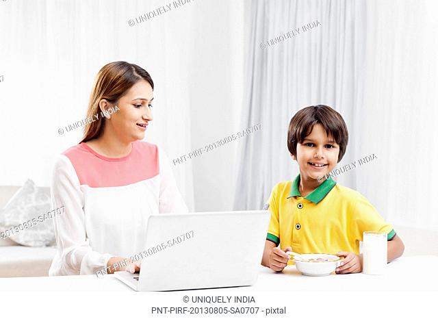 Woman using a laptop with her son having breakfast