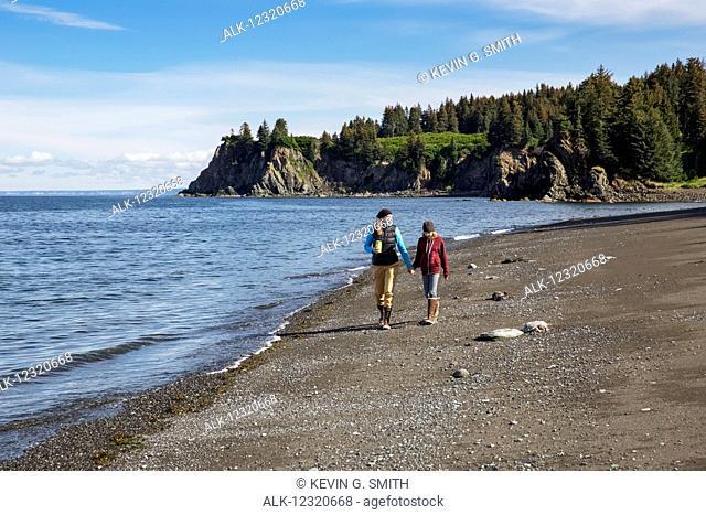 Mother and daughter walk on the beach, Seldovia, Southcentral Alaska, USA