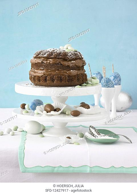 Chocolate cake on a cake stand with chocolate Easter eggs