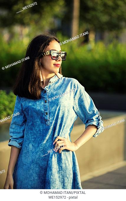 Beautiful young woman wearing sunglasses looking away