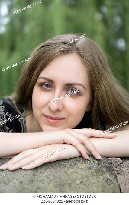 Happy young woman leaning on the wall outdoors