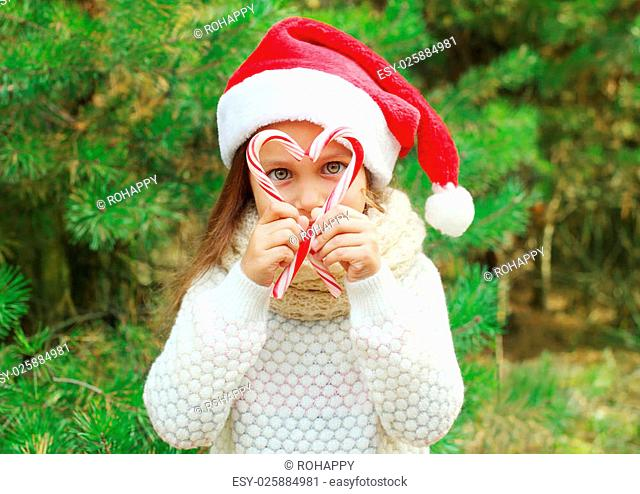 Christmas and people concept - child in santa red hat with sweet lollipop cane