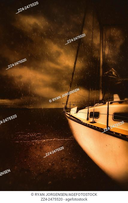 Stormy artistic portrait of the prow of a yacht beached on the shore with dramatic toned dark turbulant clouds