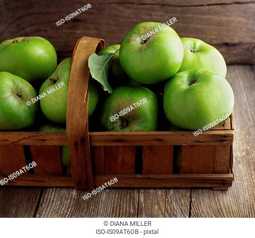 Still life of fresh green apples in basket