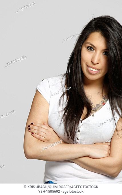 Studio shot of young Chilean woman, arms crossed
