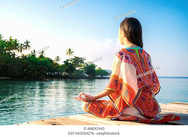 Asian girl sit and post Yoga position on the resort in thailand, this image can use for Lotus, Yoga, Thailand, beach, travel, relax , beach and Summer concept