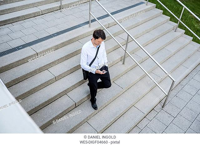 Businessman with cell phone going downstairs