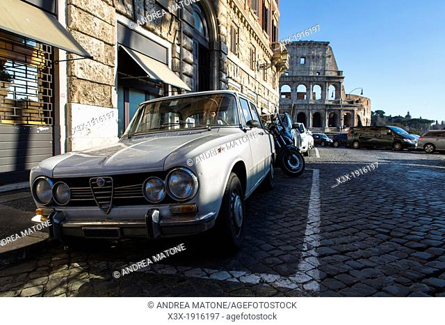 Old white Alfa Romeo car parked by the Roman Colosseum in Rome Italy
