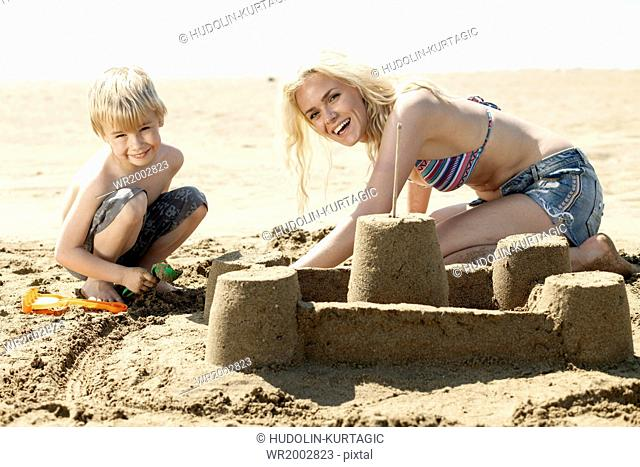 Mother and son making sandcastle on beach
