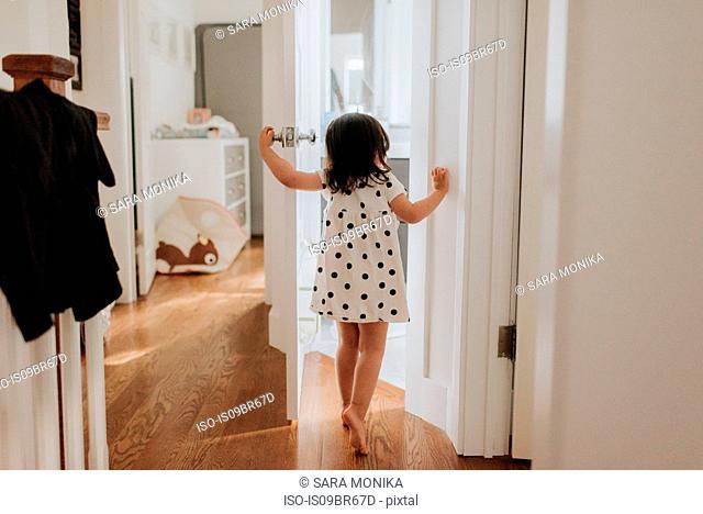 Curious girl opening door
