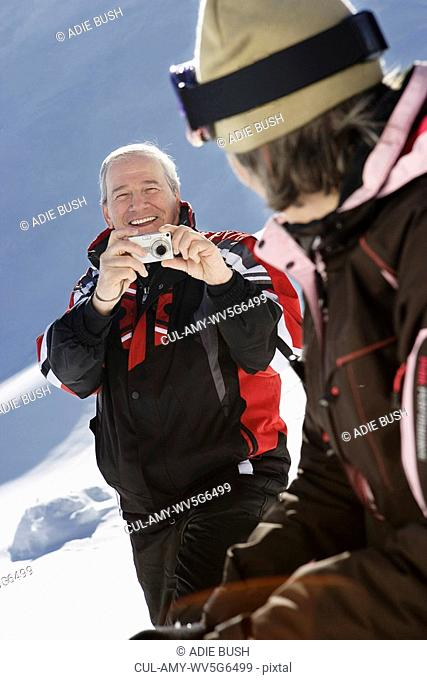 Mature man in ski-wear taking photograph of wife on mountain