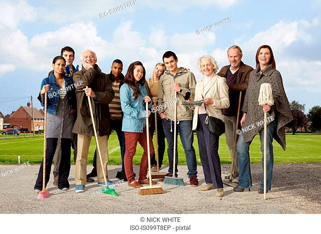 Group of people standing with brooms and mop