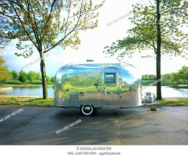 Airstream trailer parked in front of a lake