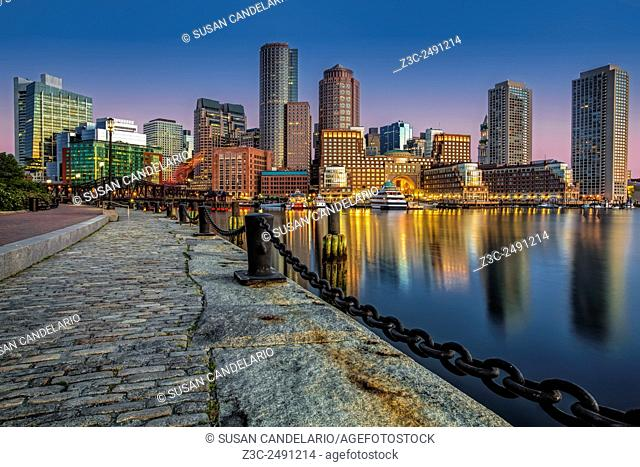 Boston Skyline Dawn - Fan Pier Boston Harbor - A view during twilight as the sun begins to rise to the Boston Harbor with the Boston Financial District's...