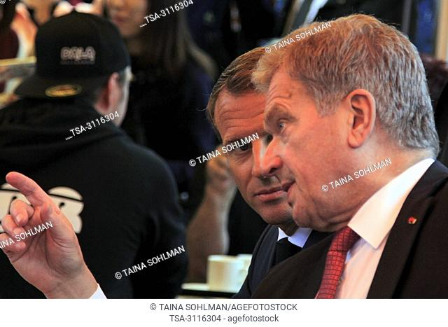 Helsinki, Finland. August 30, 2018. French President Emmanuel Macron (C) and Finnish President Sauli Niinistö (R) have a cup of coffee at a small Market Square...
