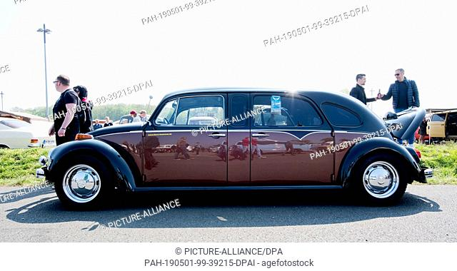 """FILED - 01 May 2019, Lower Saxony, Hanover: A VW Beetle, in a long version modified to a limousine, stands at the 36th """"""""Maikäfertreffen"""""""" on a fair parking lot"""