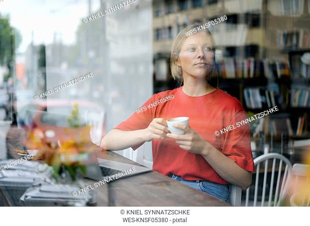 Young woman with laptop and coffee cup in a cafe