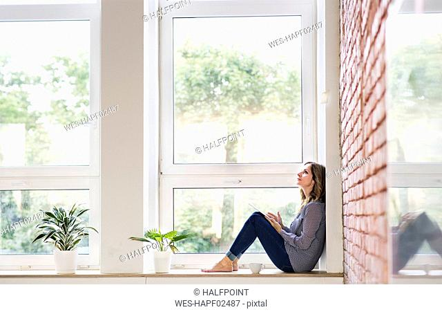 Woman sitting at home on the window sill, reading a book