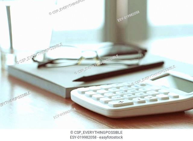 business documents on office table with calculator and digital tablet