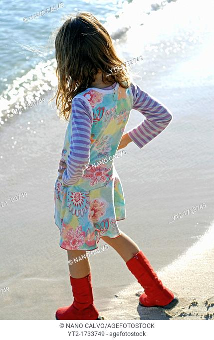 Cute brazilian seven year old girl with red boots, playing on the seashore