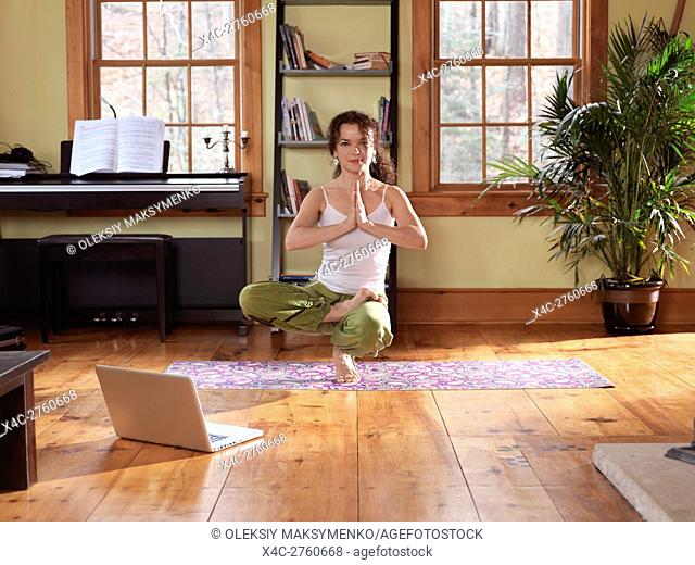 Young woman practicing yoga, balancing on one foot at home in a living room with a laptop by her side