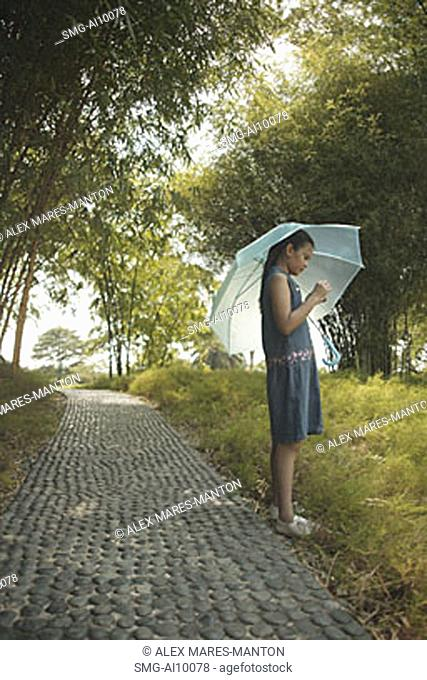 Young girl holding an umbrella, looking at something