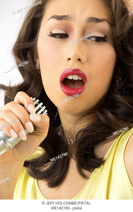 Beautiful young woman head and shoulders, singing into microphone with passion, looking aside