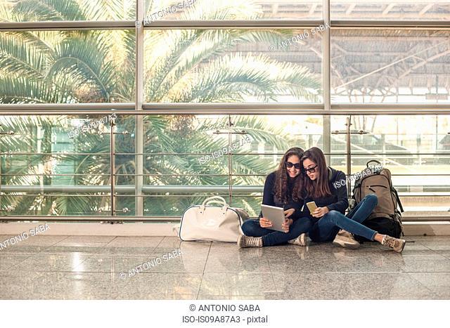 Teenage girls sitting on floor using digital tablet