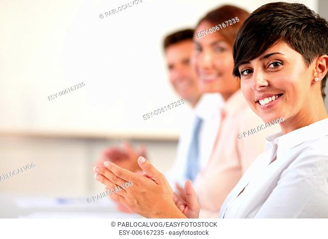 Portrait of an adult coworker team smiling and giving applause while looking at you on office - copyspace