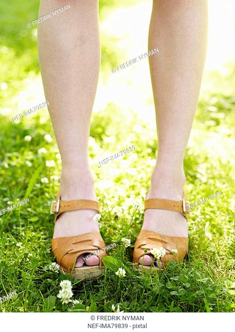 The feet of a woman standing in the grass