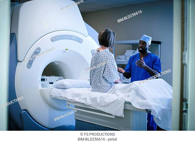 Technician talking to patient at scanner