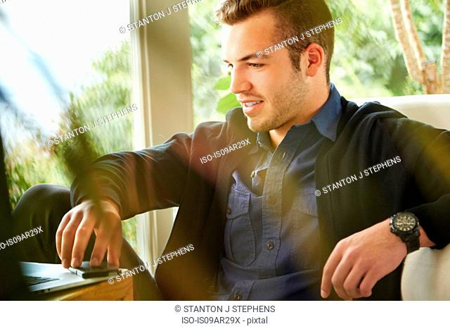 Portrait of man sitting on floor using laptop