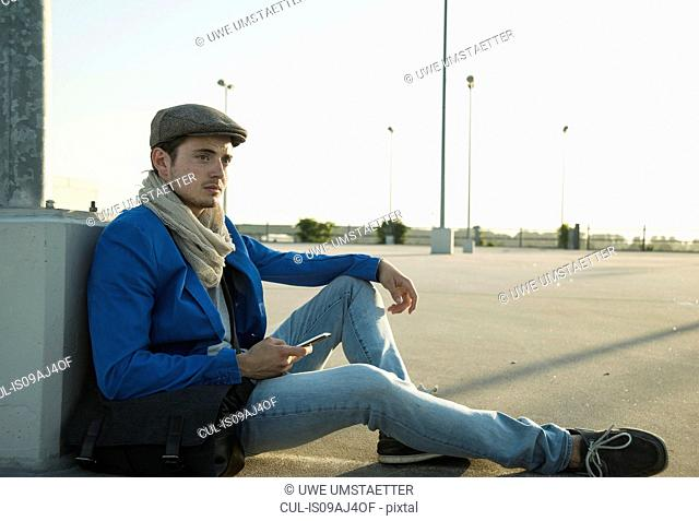 Young man with smartphone waiting in empty parking lot