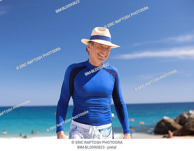 Smiling Caucasian man standing on beach