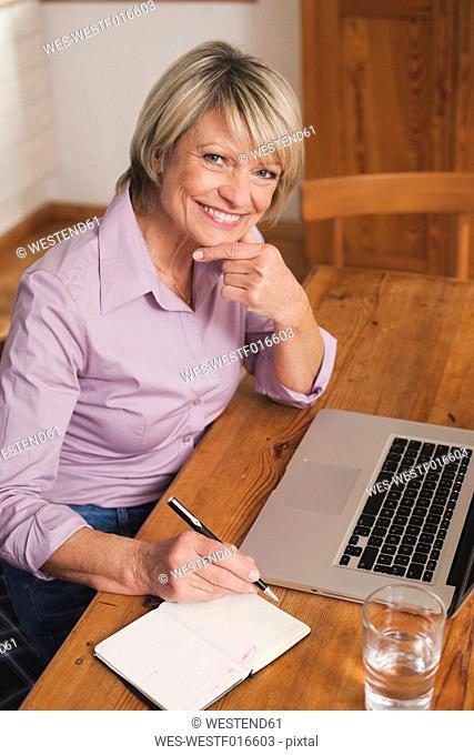 Germany, Kratzeburg, Senior woman with diary and laptop, smiling, portrait