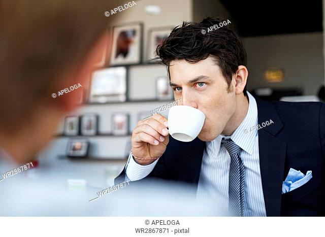 Handsome businessman having coffee at cafe