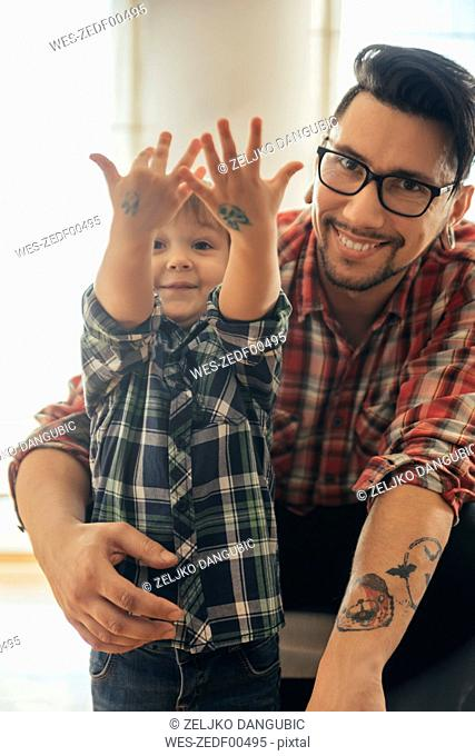 Proud son showing painted tattoos on his hands
