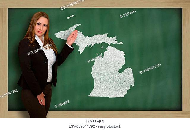 Successful, beautiful and confident young woman showing map of michigan on blackboard for presentation, marketing research and tourist advertising