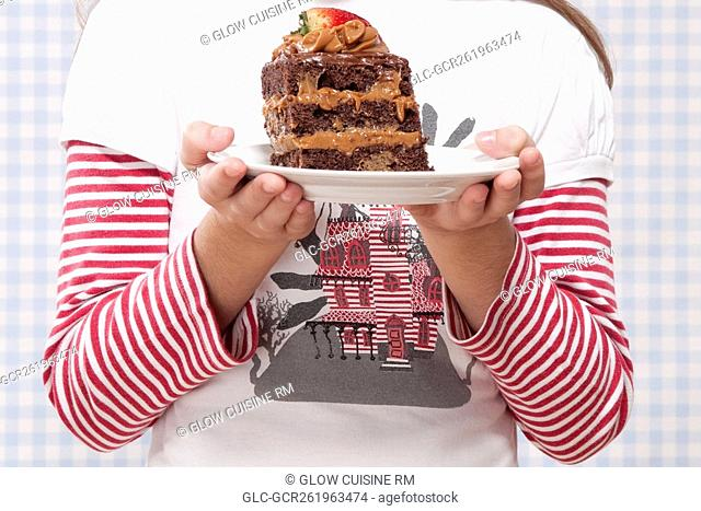 Mid section view of a girl holding a plate of chocolate pastry