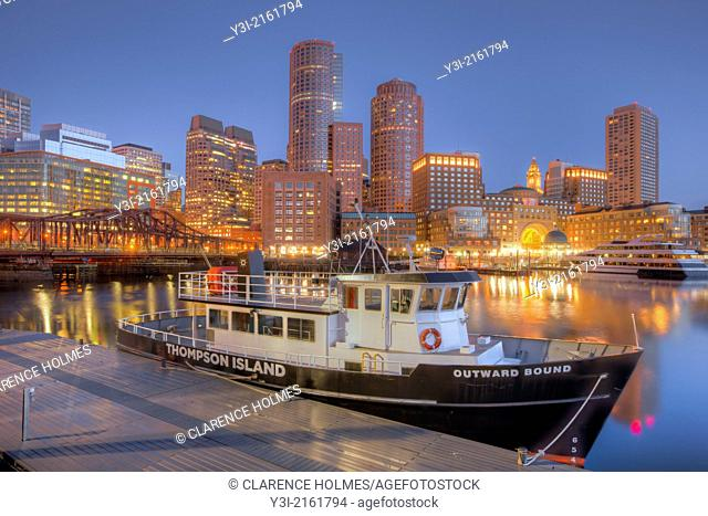 The Outward Bound Thompson Island Ferry sits moored in front of the skyline in the last hour before sunrise as a new day begins in Boston, Massachusetts, USA