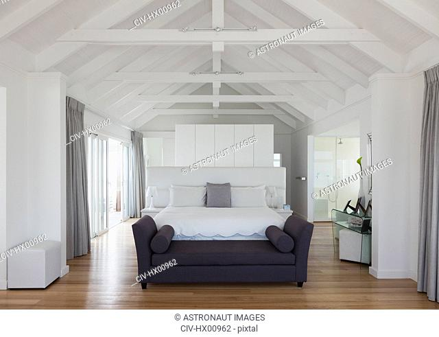 White vaulted wood beam ceiling over bed in home showcase interior