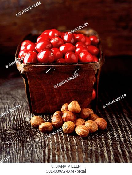 Food, rustic punnet full of cranberries and hazelnuts, wooden table