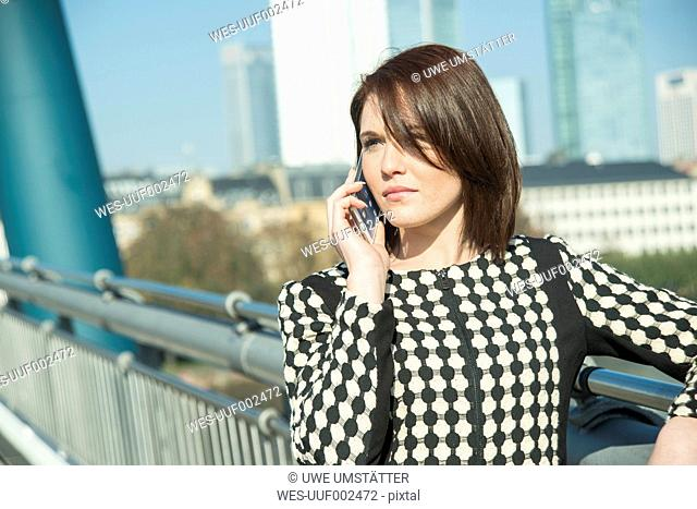 Germany, Frankfurt, young businesswoman on bridge on cell phone