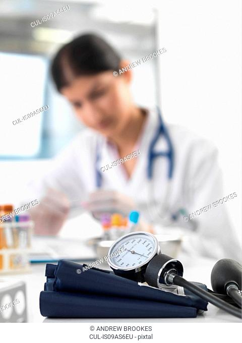 Female doctor examining test tube at desk in clinic