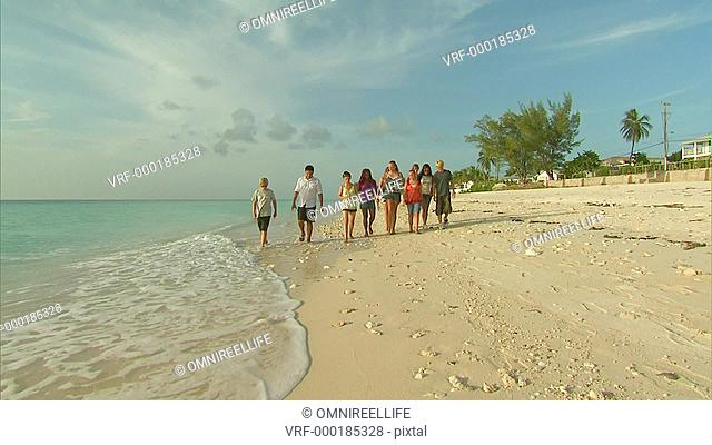 Ten teenage females and males walking along white sandy beach next to tide towards camera with Palm Trees and ocean to the sides and looking out to sea